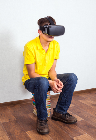 Young Man in Virtual Reality Headset on the Floor with a Books Stock Photo