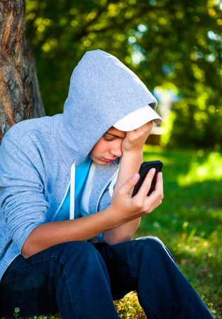 Sad Teenager with Cellphone in the Summer Park Stock Photo