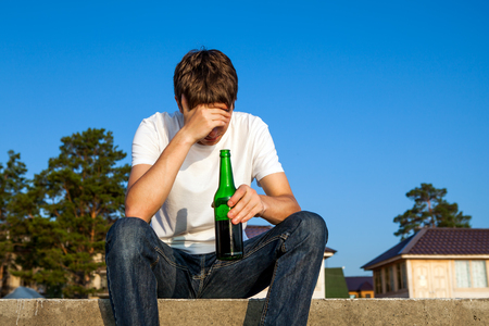 Sad Young Man with a Beer on the Street