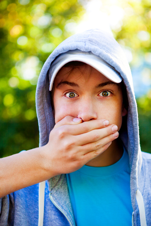 Teenager close his Mouth in the Summer Park Stock Photo