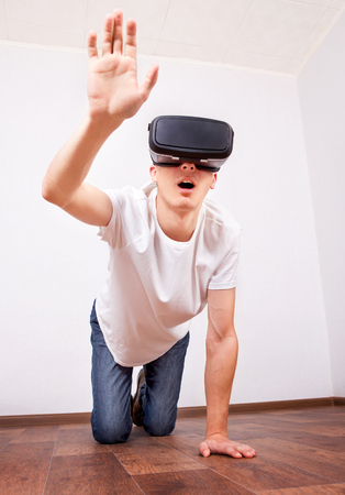 Young Man in Virtual Reality Headset on the Floor in the Empty Room Reklamní fotografie