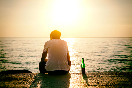 Toned Photo of the Man with a Beer sit at Seaside on Sunset Background 版權商用圖片