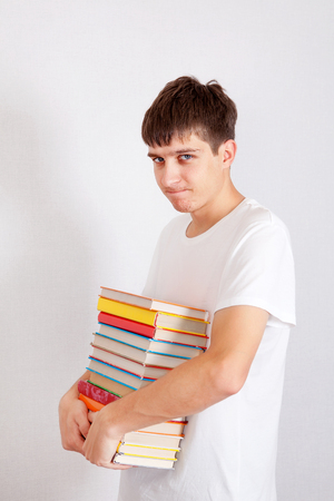 Displeased Student with the Books on the White Wall Background Stock Photo