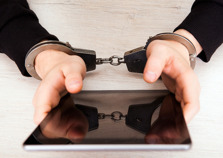 Person in Handcuffs hold a Tablet Computer on the Table closeup