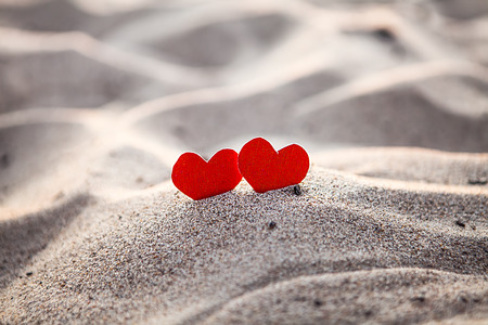 Two Red Hearts in the Sand closeup Stock Photo