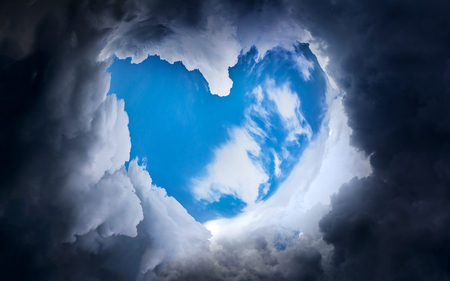Heart Shape with Blue Sky in the Dramatic and Storm Clouds Stock Photo