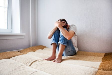 Sad Young Man on the Couch in the Room
