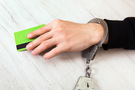 Person in Handcuffs with a Bank Card on the Table closeup Stock Photo