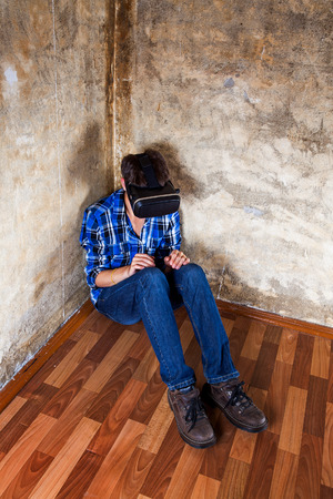 Young Man in Virtual Reality Mask sit on the Floor in the Corner 免版税图像