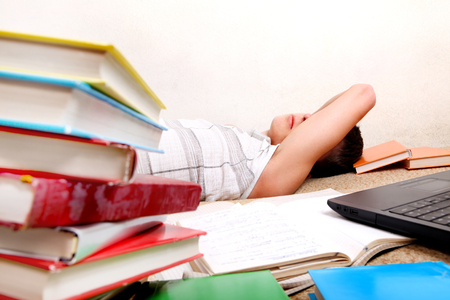 Tired Student sleep with a Books on the Sofa in the Room