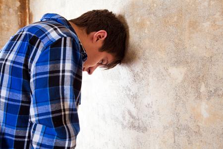 Jeune homme triste près du vieux mur