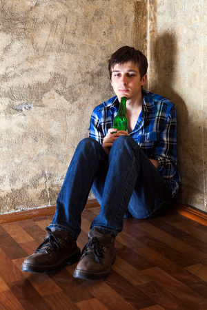 Sad Young Man with a Beer in the Corner by the Old Wall Banque d'images