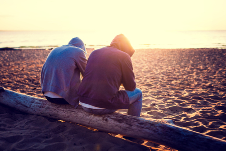 Toned Photo of Two Men on the shore at Sunset