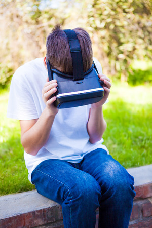 Man in Virtual Reality Glasses sit in the Summer Park
