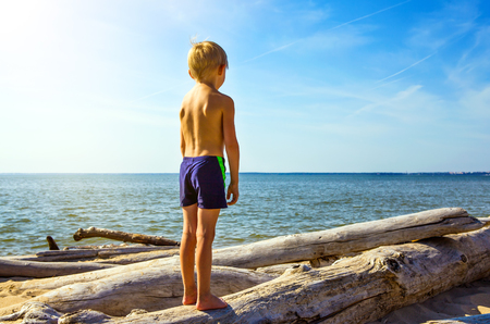 Little Boy stand on the Log on the Sea Background