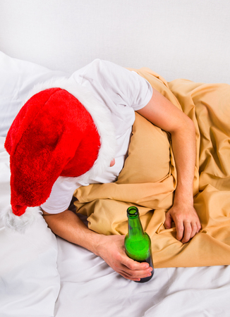 Man in Santa Hat in the Bed with a Beer Bottle