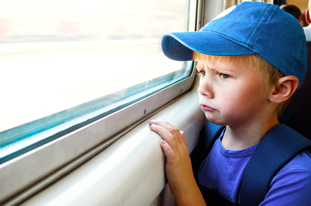 Sad Child Boy sit in the Train by the Window Banco de Imagens