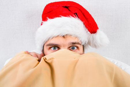 Frightened Young Man in Santa Hat under Blanket in the Bed at the Home