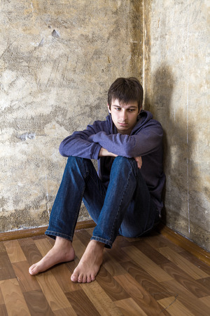 Barefoot Sad Young Man in the Corner on the Floor by the Old Wall Foto de archivo