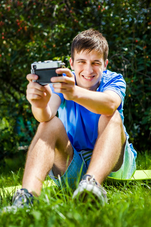 Happy Young Man take a Selfie with a Vintage Camera on the Grass outdoor Banco de Imagens