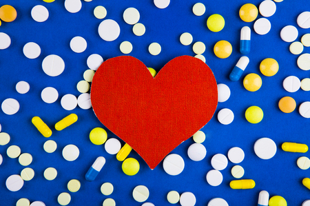 Red Heart Shape with a Pills on the Blue Paper Background 스톡 콘텐츠
