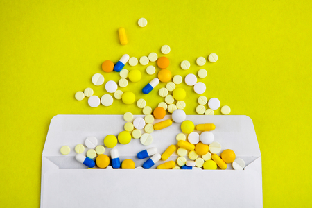 Pills with an Envelope on the Yellow Paper Background closeup Stok Fotoğraf