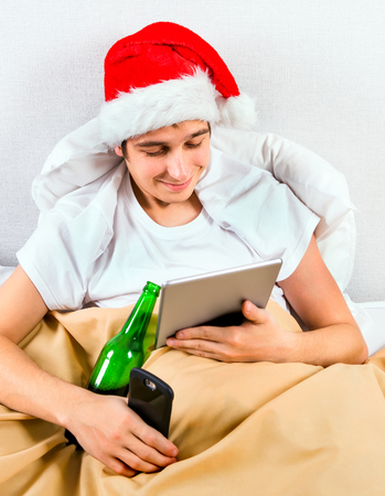 Young Man in Santa Hat with a Tablet Computer and a Phone and a Beer Bottle in the Bed