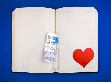 Blank Writing Pad with Heart Shape and Empty Pack of the Pills and a Syringe on the Blue Paper Background closeup Stock Photo