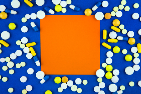 Pills and Empty Orange Paper on the Blue Cardboard Background