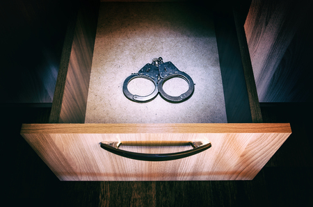 Handcuffs in the Opened Drawer of the Furniture