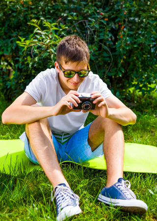 Happy Young Man with a Vintage Camera on the Grass outdoor