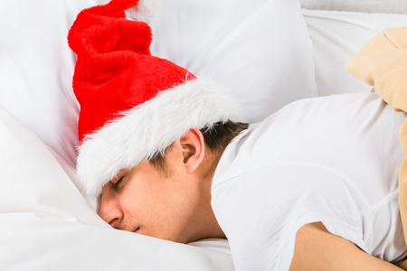 Tired Young Man in Santa Hat sleep in the Bed at the Home 写真素材
