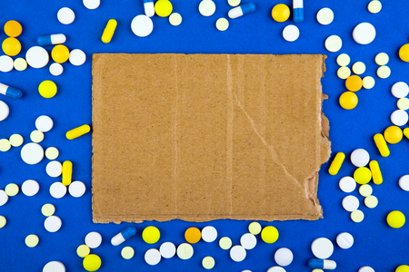 Pills and Empty Old Cardboard on the Blue Paper Background