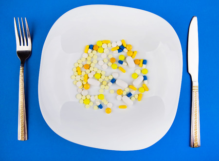 Pills in the Plate with a Cutlery on the Blue Paper Background