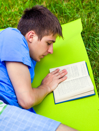 Young Man read a Book on the Summer Meadow Banco de Imagens - 121336042