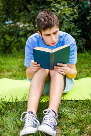 Surprised Young Man read a Book on the Grass
