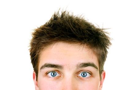 Primer plano de la cara del joven sorprendido en el fondo blanco