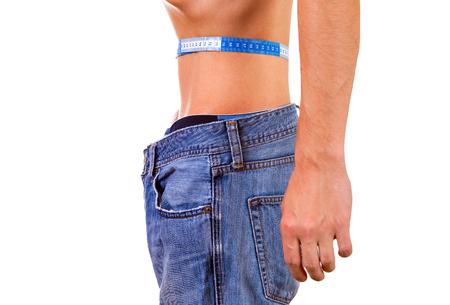 Hombre flaco en jeans mide su cintura en el primer plano de fondo blanco Foto de archivo