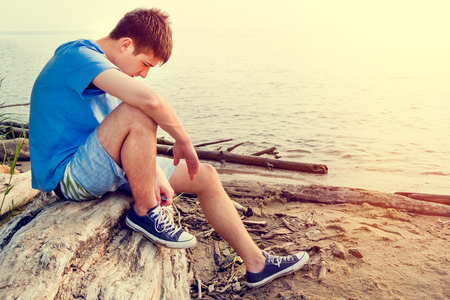 Toned Photo of Sad Young Man sit on the Log at the Seaside
