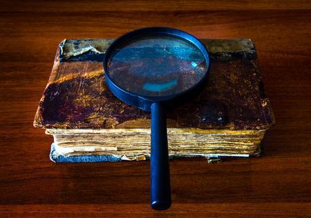 Libro antiguo con una lupa en el primer plano de la mesa