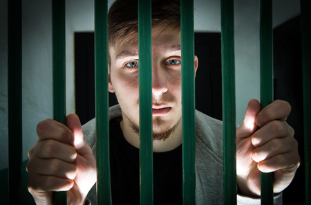 Jailed Young Man behind bars in a Cell Reklamní fotografie