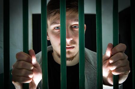 Jeune homme emprisonné derrière les barreaux dans une cellule Banque d'images