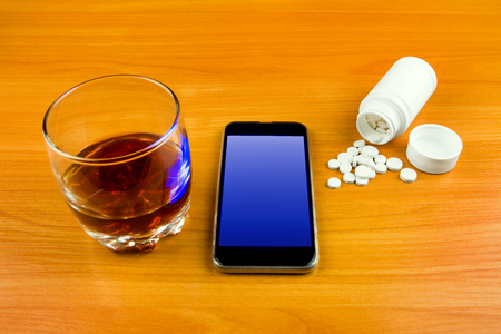 Glass of the Whiskey with a Pills and the Phone on the Table closeup
