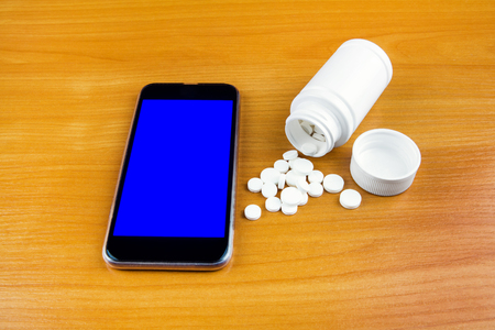 Mobile Phone with a Pills on the Wooden Table closeup 免版税图像