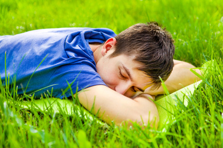Young Man sleep on the Grass of the Summer Meadow