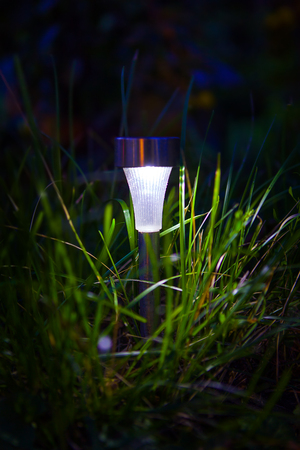 Solar Powered Lamp in the Grass in the Night Stock Photo