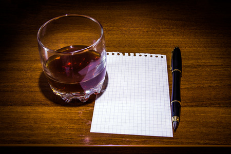 Glass of the Whiskey and Empty Paper on the Table closeup