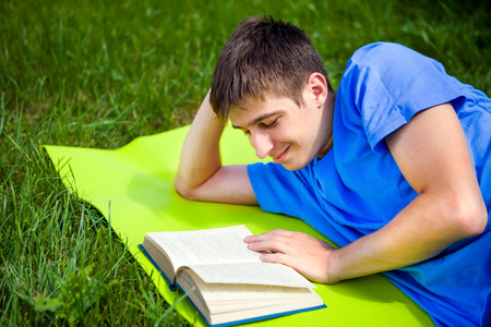 Happy Young Man read a Book on the Summer Meadow Banco de Imagens - 121335014