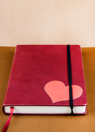 Red Book with a Heart Shape on the Brown Paper Background closeup