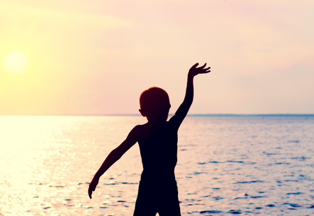 Toned Photo of Child Silhouette waving his Arm on the Sea Background